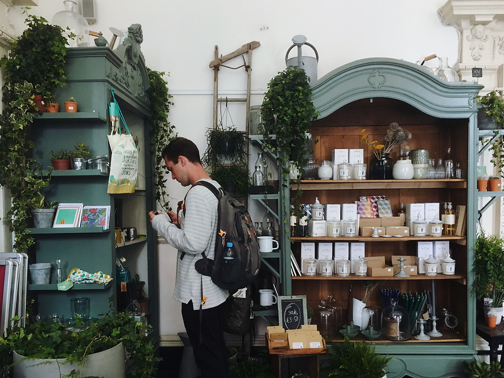 photo shows the inside of a shop with gifts on the shelves and a man looking at them