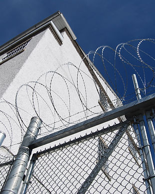 A tall fence with barbed wire on top surround a jail