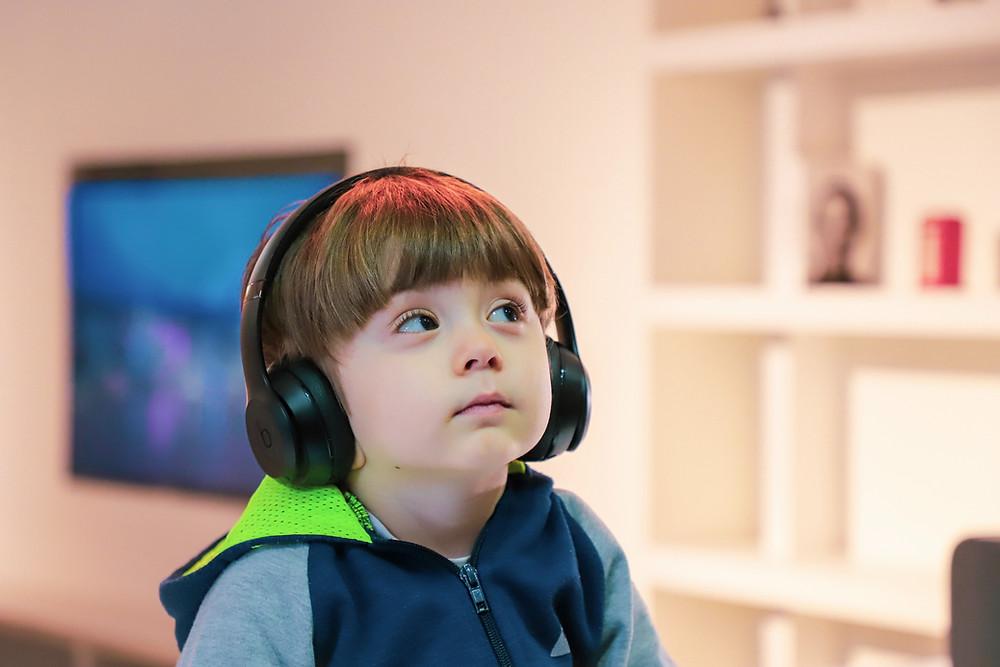 garoto de aproximadamente quatro anos sentado de forma calma com fones de ouvido