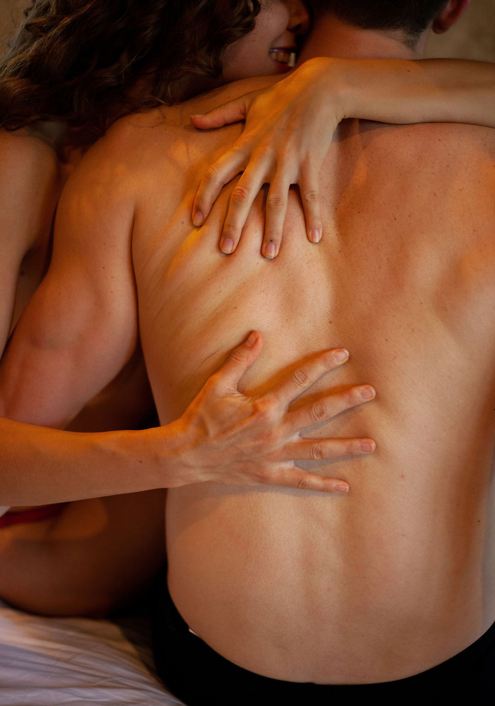 Couple in love having sex, showing the back of the man lying on the woman while she is whispering in his ears