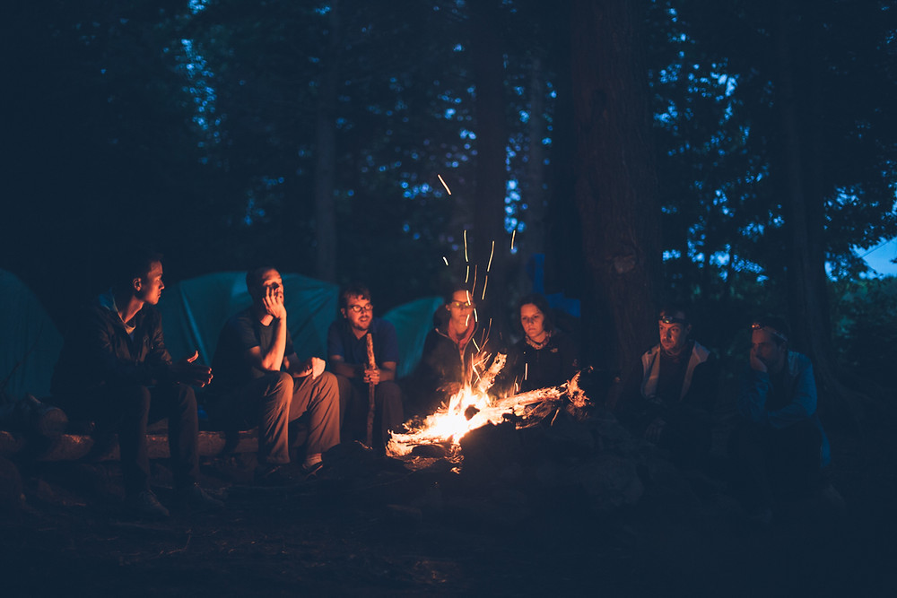 Men and women sitting around a campfire in a forest.