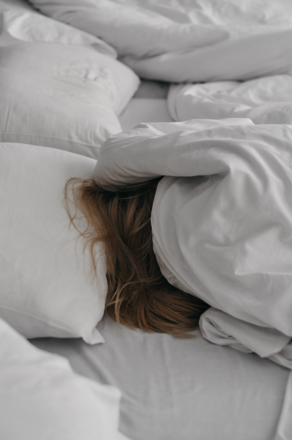 Person in bed with covers over head and sunlight shining on the bed.