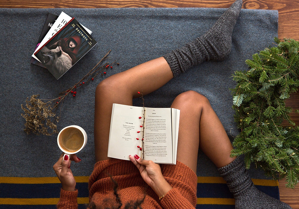 A girl is sitting on a blanket with a book in one hand and a cup of coffee in the other