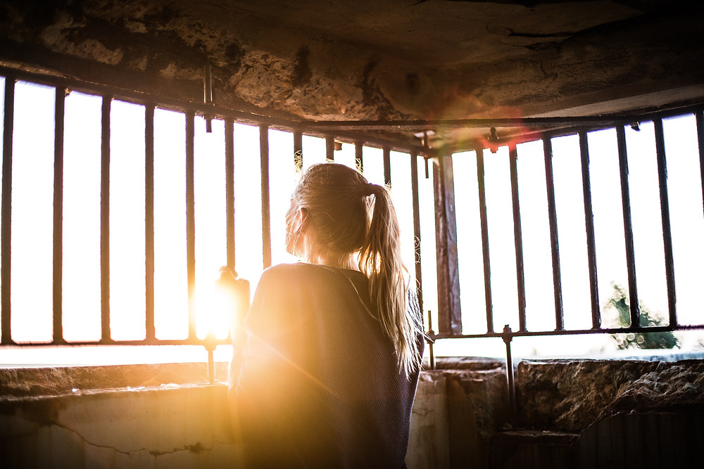 A woman standing inside a cage looking out. We can see the back of her head and she can see the light coming in from outside her bars: Mental torment.