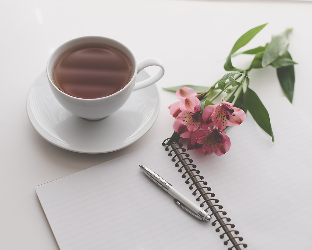 open journal and pen next to some pink flowers and a cup of tea