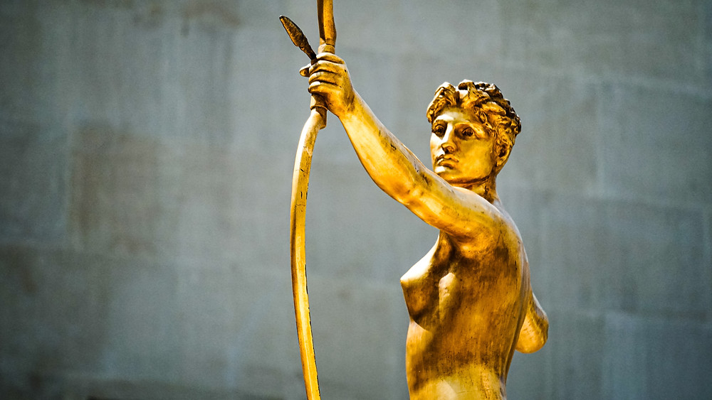 Gold statue from waist up of Greek goddess with bow and arrow