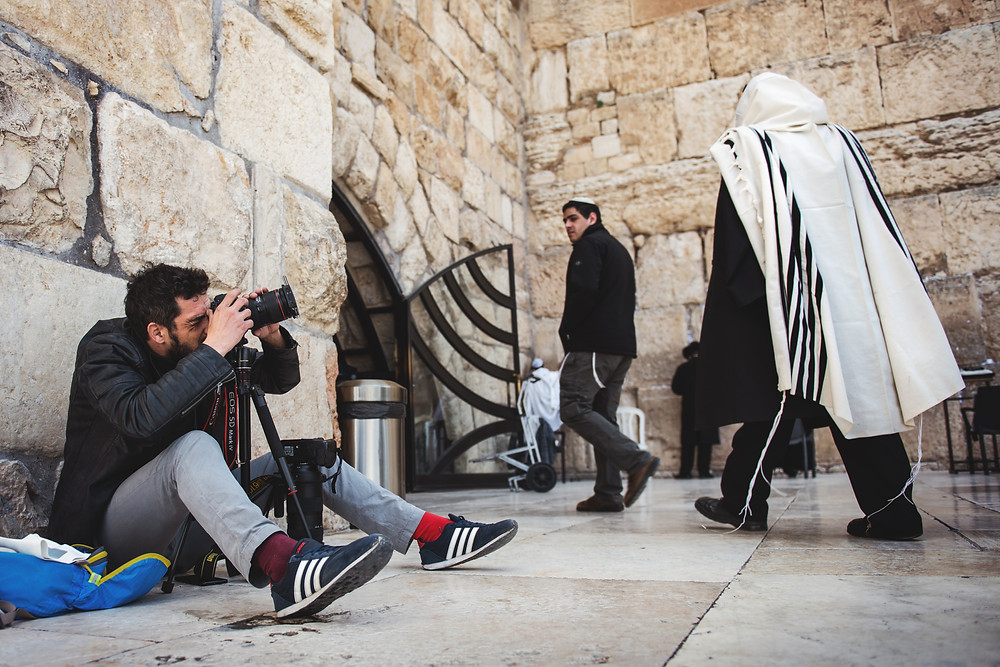 A young man photographing Jewish men at the Western Wall