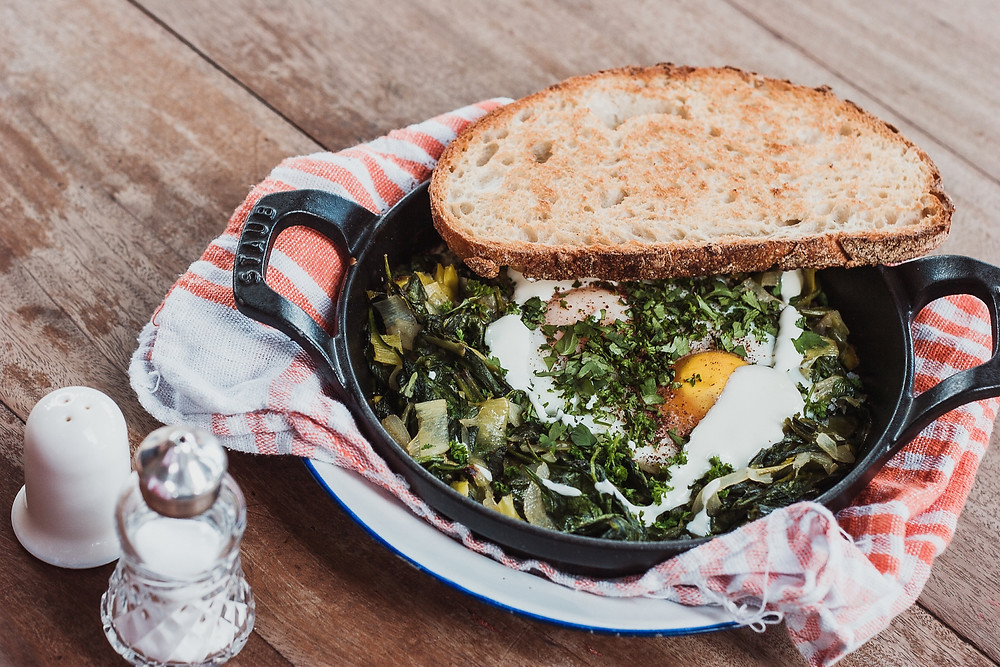 mixed greens with eggs in skillet