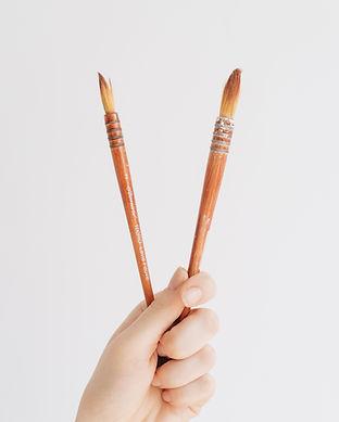 Hand holding paint brushes, Jenna Archer Ceramics, Calgary, Canada