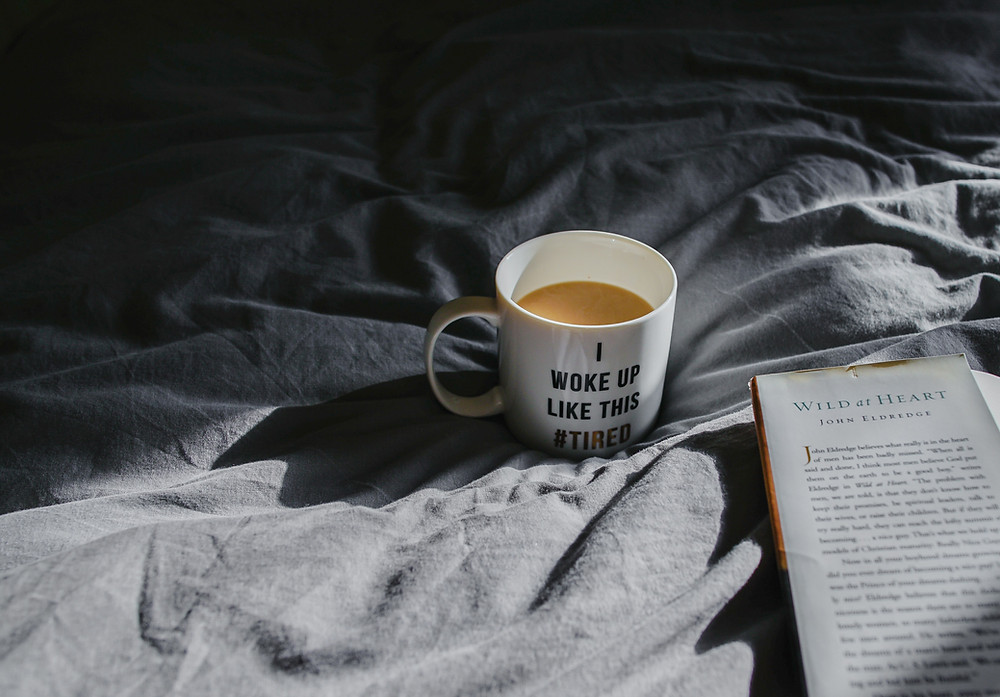 can't sleep, messy bed, with coffee mug and novel