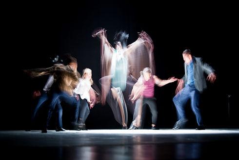Ihmiset lavalla kovassa liikkeessä, keskimmäinen ihminen hypähtää, näkyy heijastuksena