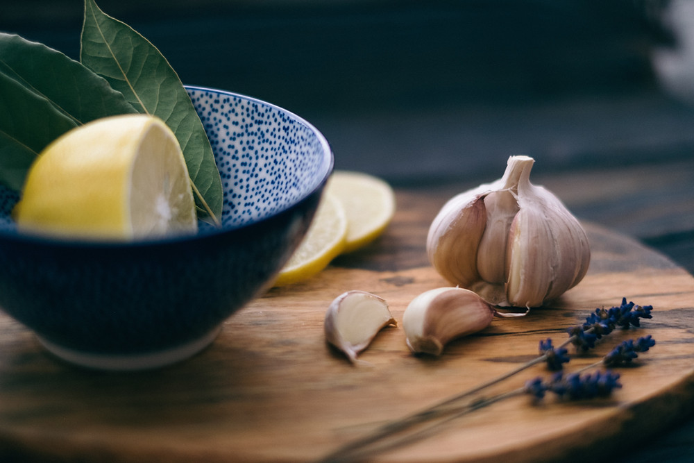 Lemons in a blue bowl sitting on a table with whole garlic cloves.