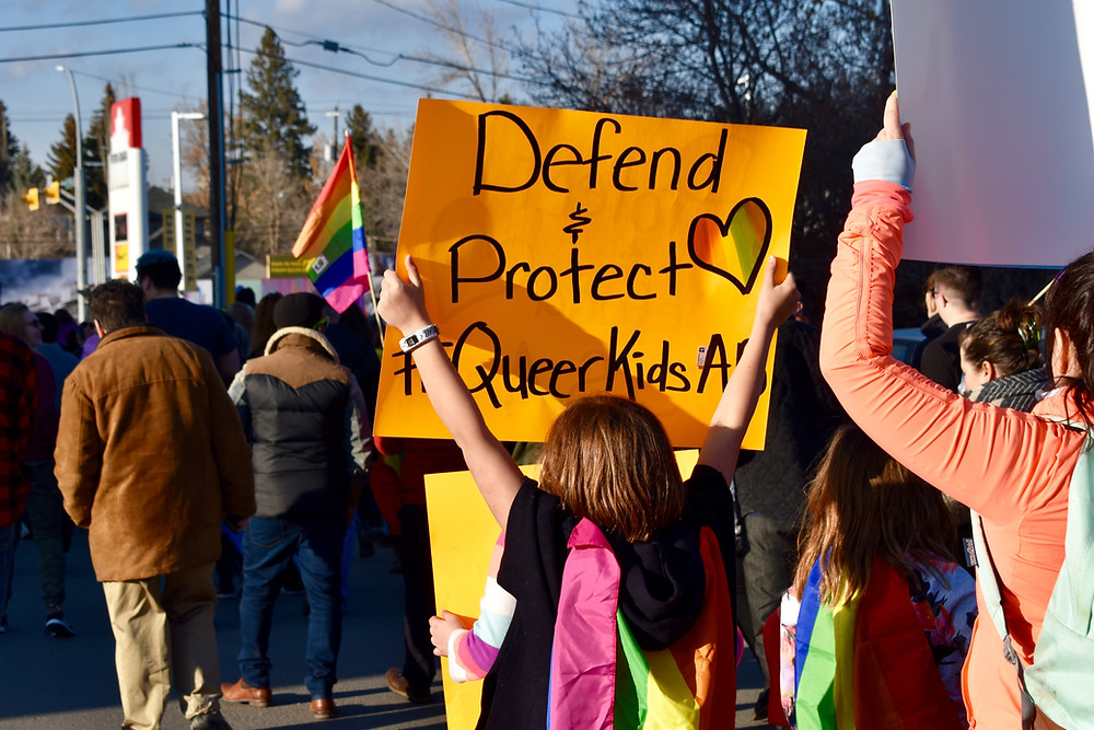 Child holding a sign at a protest that reads Defend & protect Queer Kids