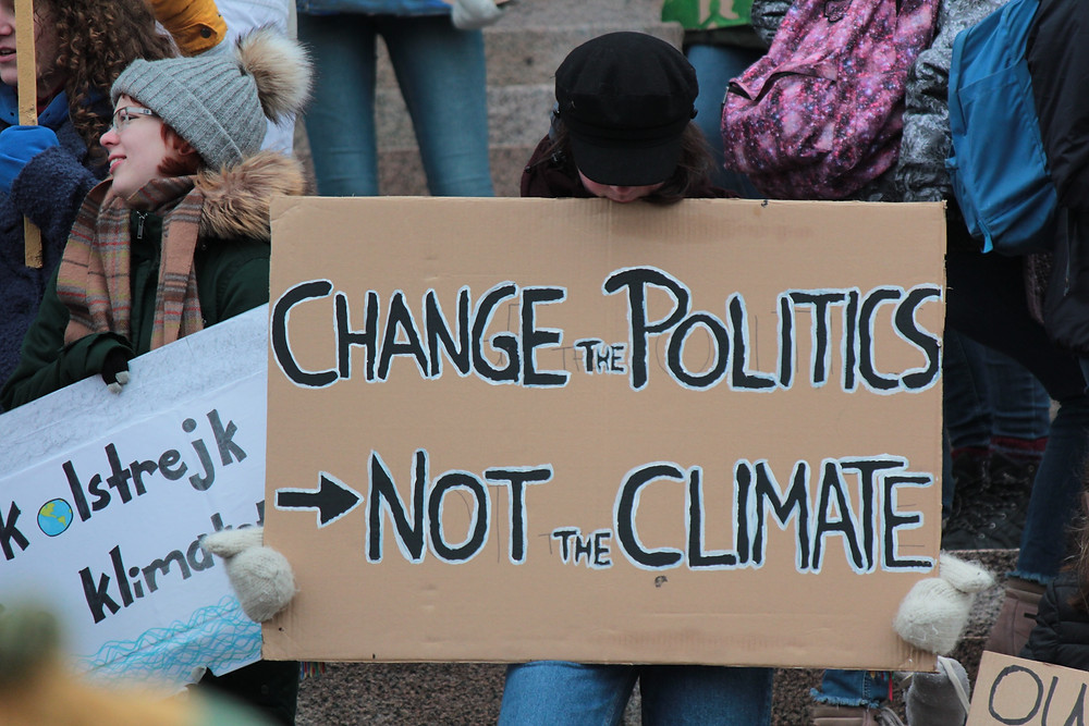 """Protest sign """"Change the Politics, Not the Climate"""""""