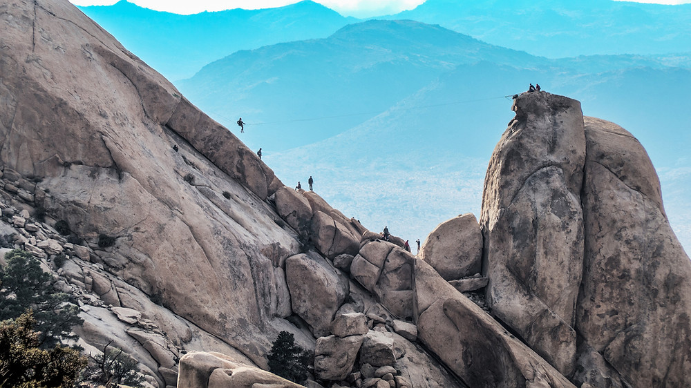 Man on a tightrope between a large boulder and a stone mountain.