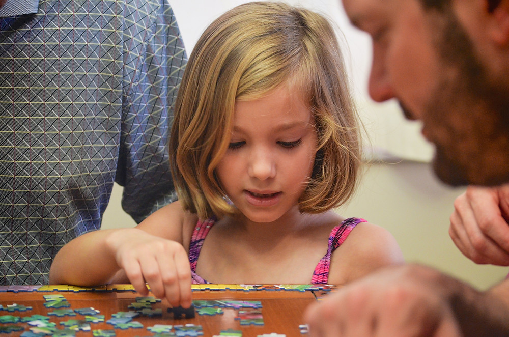 Families play games during family game night during COVID in the winter.Catalyss Counseling provides treatment for postpartum depression in Colorado through online therapy and in person counseling in the Denver area 80209 and 80210
