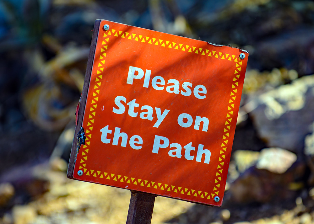"""An outdoor sign reads, """"Please stay on the path."""""""