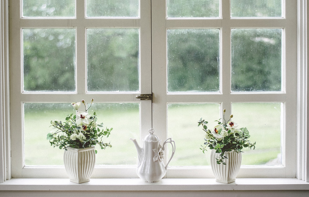 rustic white windowsill with flower pots and tea kettle looking into field