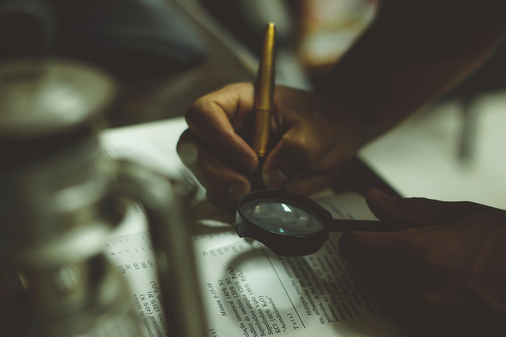 A person looking at a book through a magnifying glass