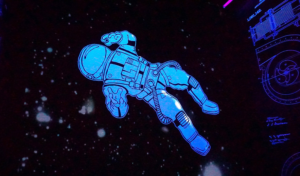 Image of a paper cutout of a drawn astronaut against a dark background that has light patches which look like stars and galaxies. The astronaut's arms are raised in a manner suggesting panic. The visor blocks their facial expression. In the foreground of the image there is an illustration in feint blue colour that looks like a blueprint or computer screen.
