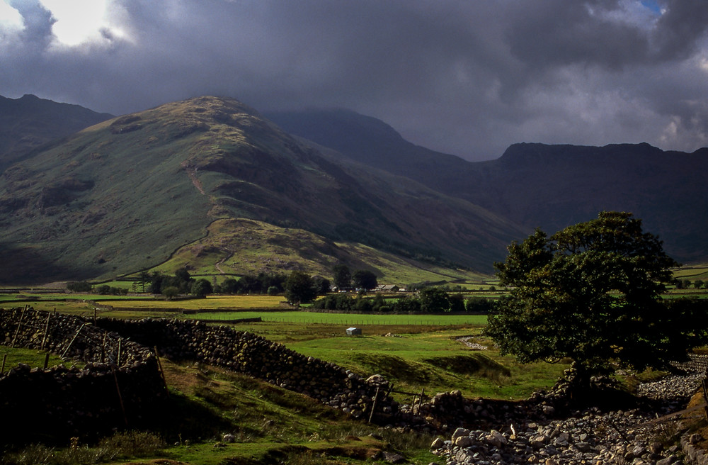 A Lake District Style Scene with a Dry Stone walled road in the foreground and Rugged Fells in the back ground.  The Sky over the Fells looks stormy and is a dark watery grey.  There is a tree in full leaf in the foreground, and in the mid distand to the right, you can see a small hamlet of cottages