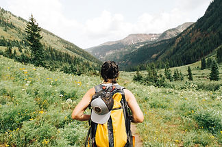 Young woman with backpack hiking through alpine meadow.Image by Holly Mandarich.
