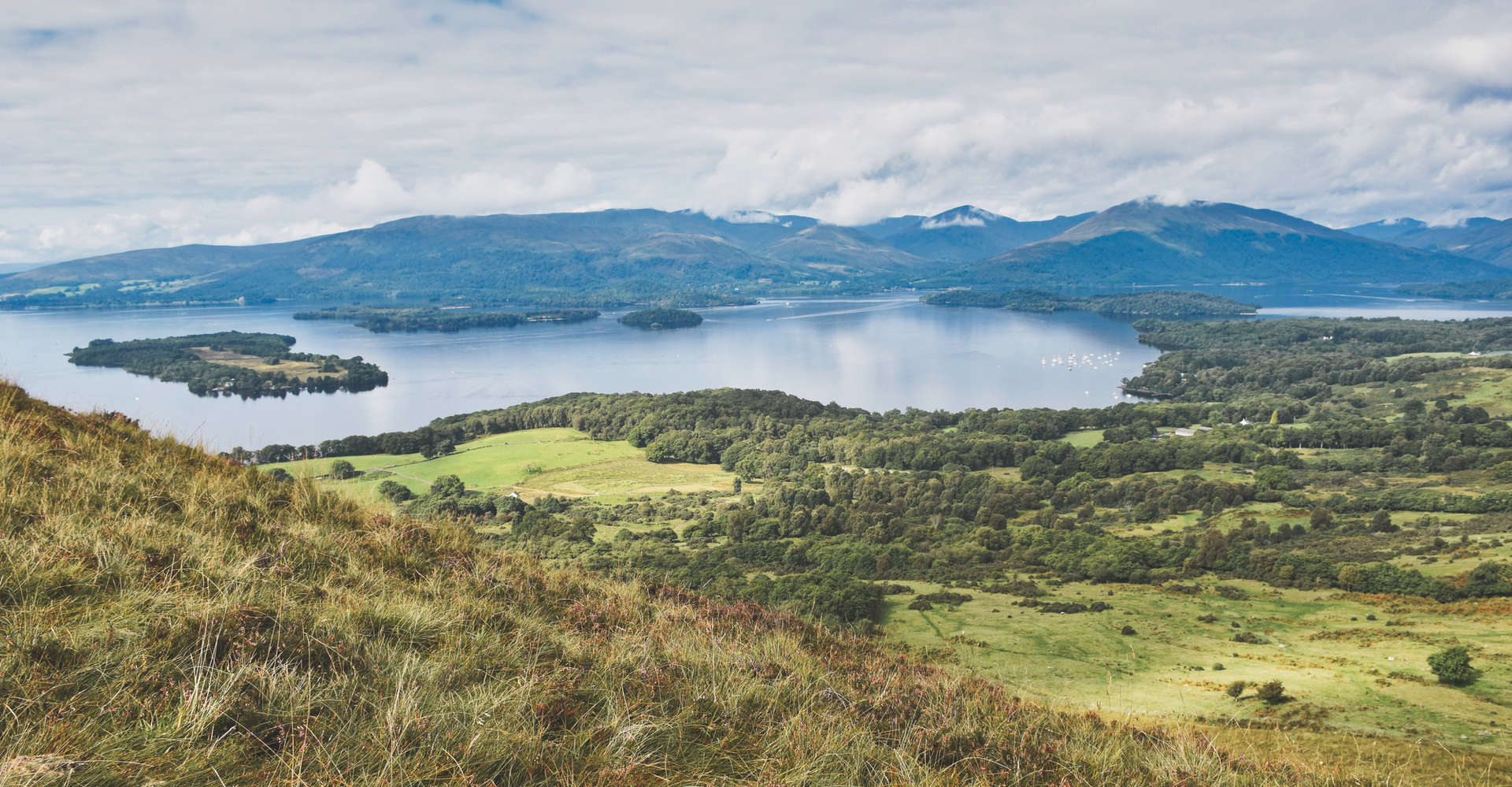 view of loch lomond from hillside showing mountains and sky