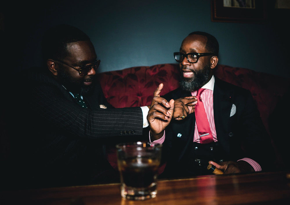 Two black men in suits laugh and talk together while drinking alcohol in a pub