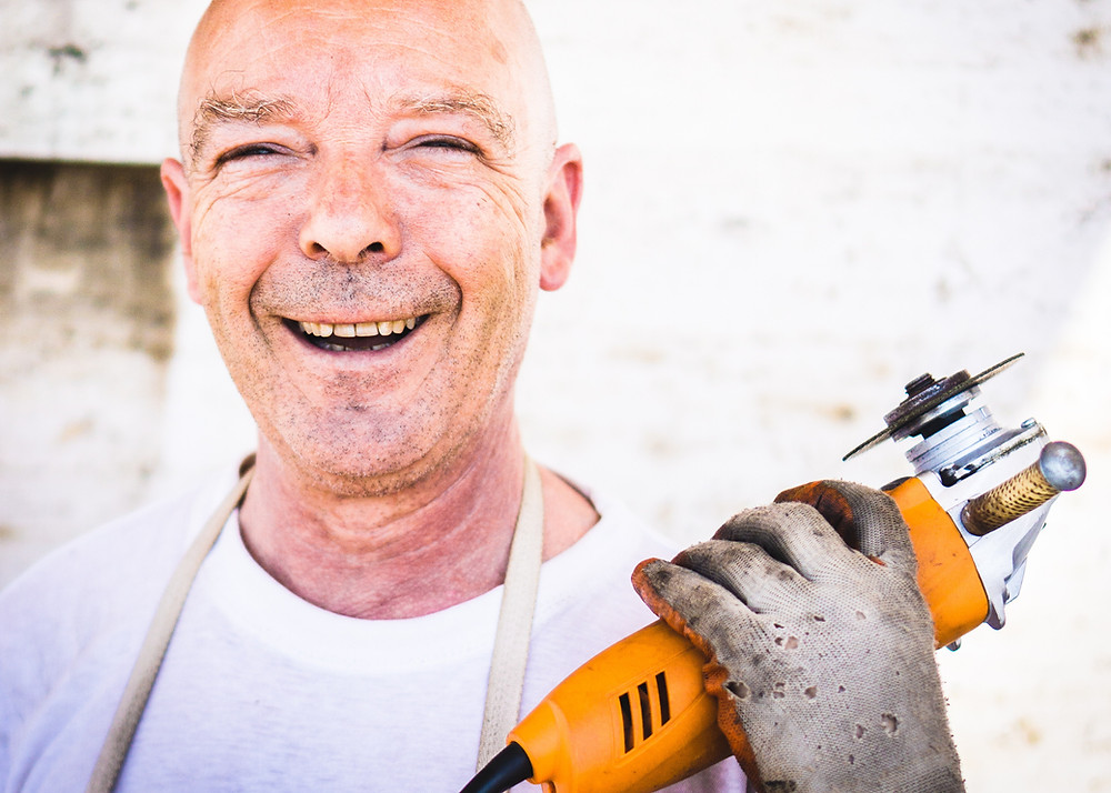 smiling caucasian man with power tools in hand looking into the camera