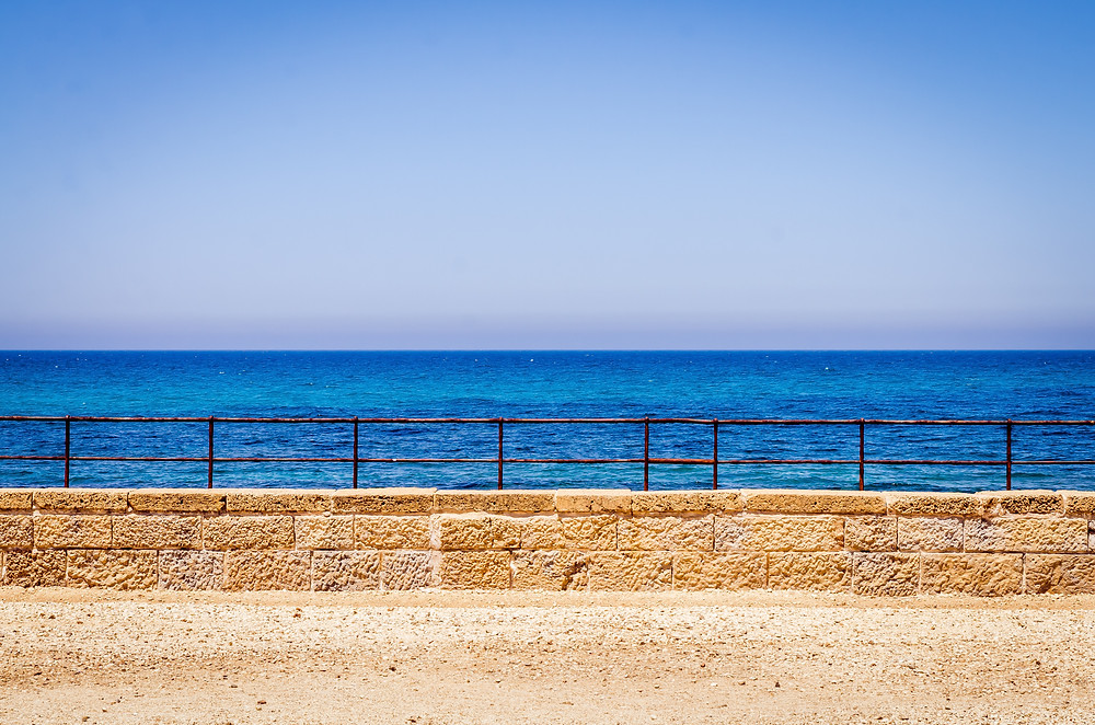Stone wall with metal railing overlooking the sea