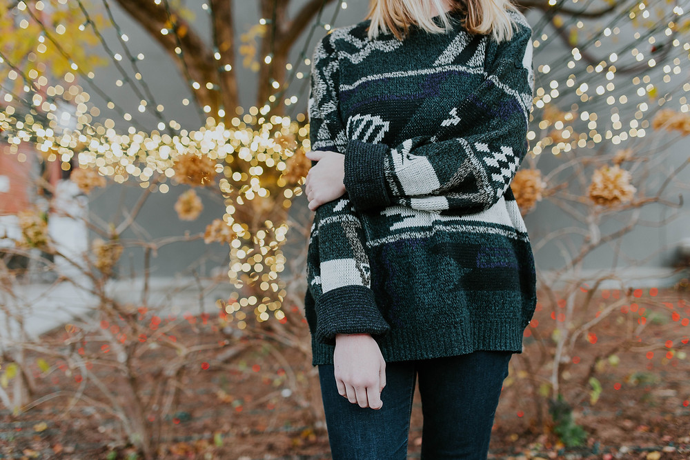 woman standing in front of lights wearing a christmas sweater