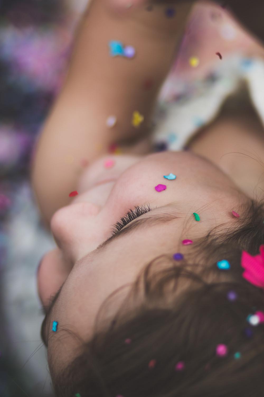 Kind mit Glitzersteinen in verschiedenen bunten Farben, Kinderwillkommensfest feiern.