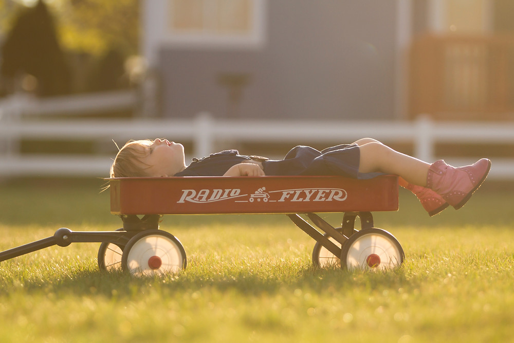 Radio Flyer red kids wagon with child relaxing and Peninsula Family Coaching