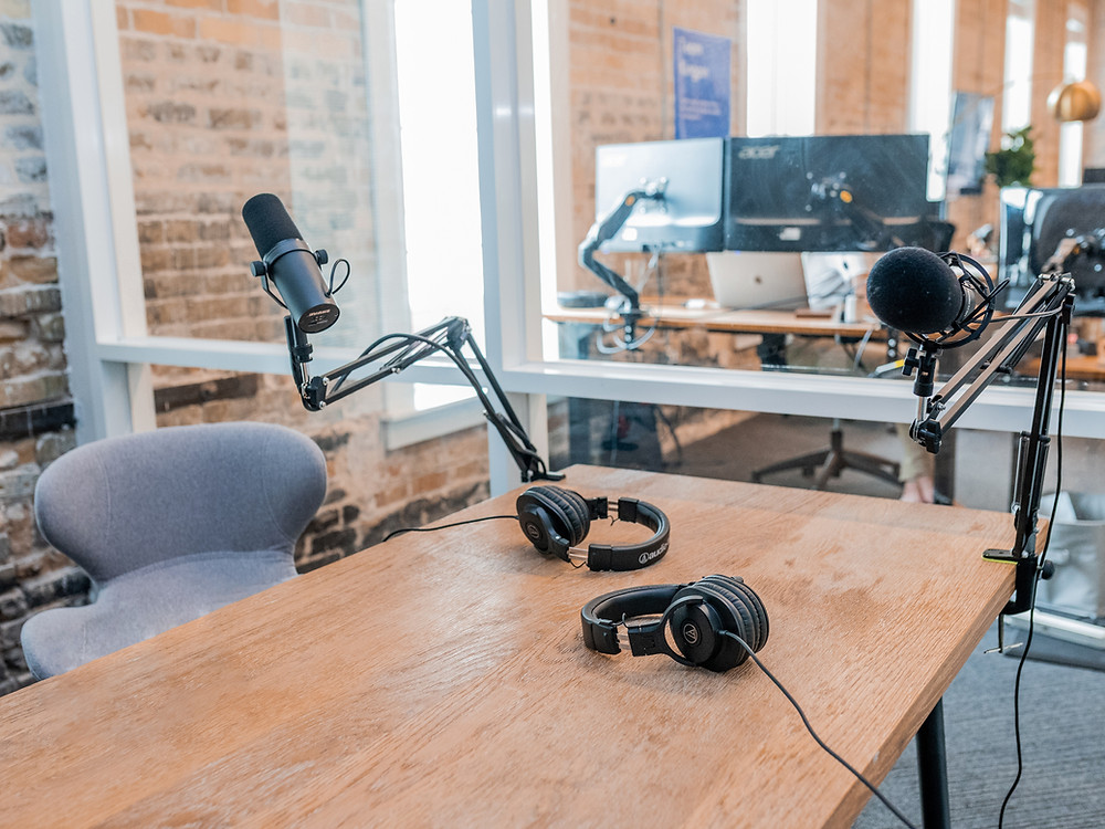 microphone and headphones set up for podcasting on an oak wood table
