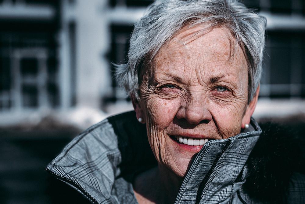 mulher idosa sorrindo em primeiro plano, segundo plano há casas desfocadas