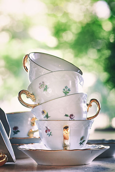 Porcelain teacups stacked up with gold handles and floral designs