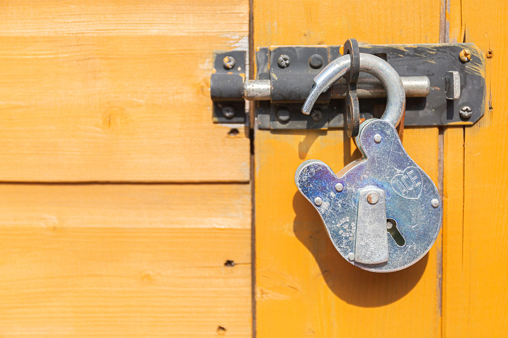 an open silver metal padlock on a door bolt, the bolt is attached to a yellow painted wooden slatted door