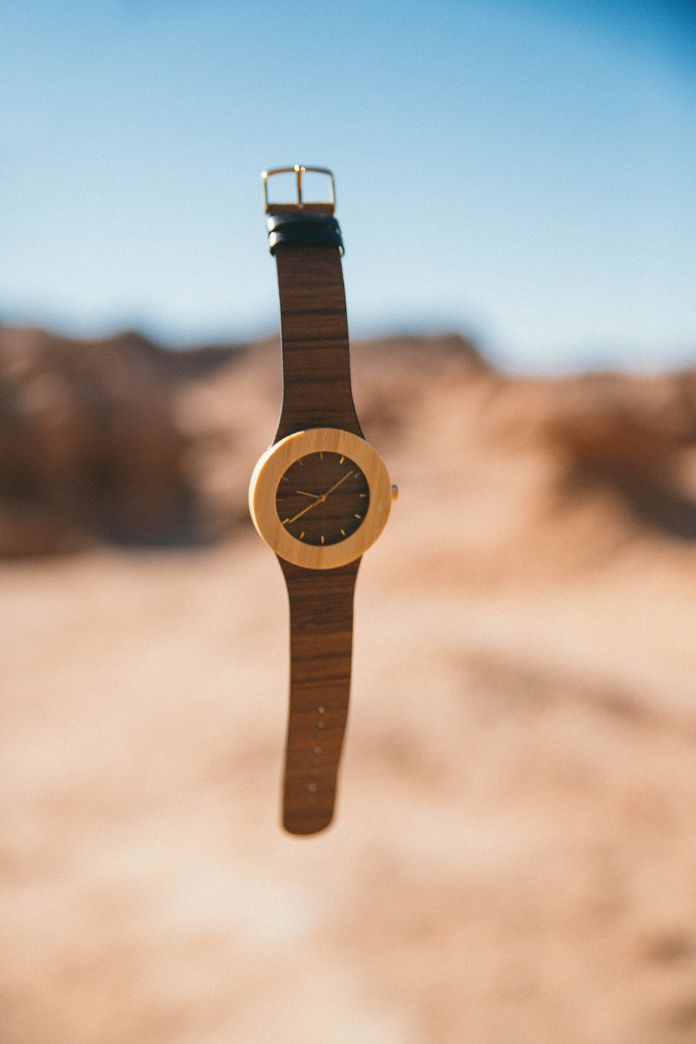 watch with leather strap and gold face floating above a desert scene