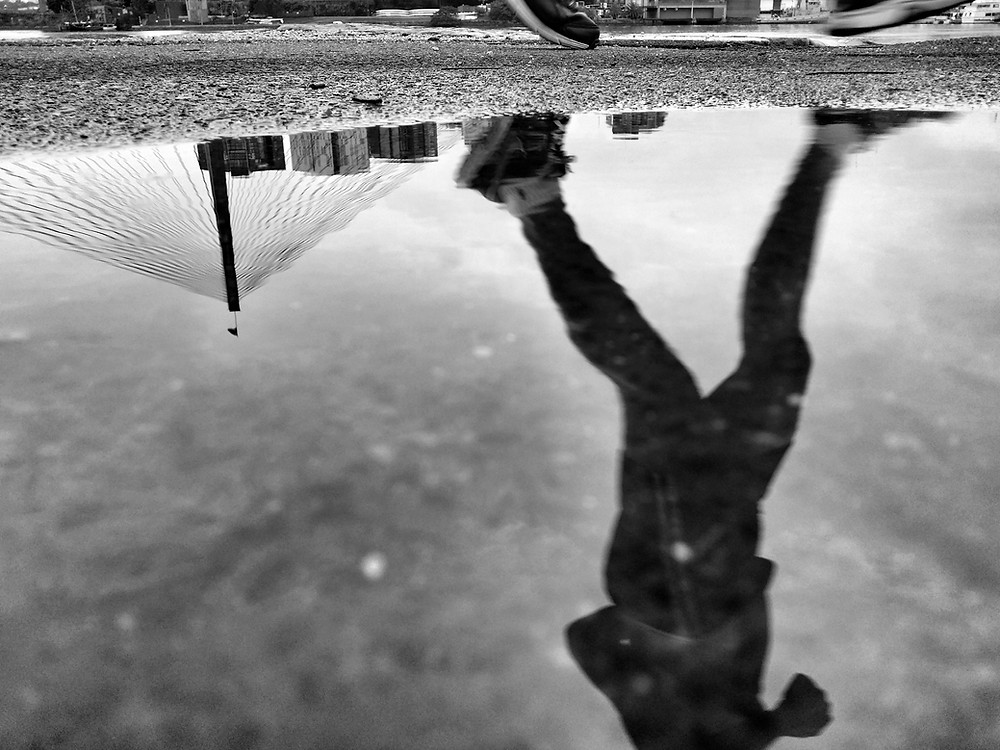 reflection of a runner in a puddle. the photo is black and white
