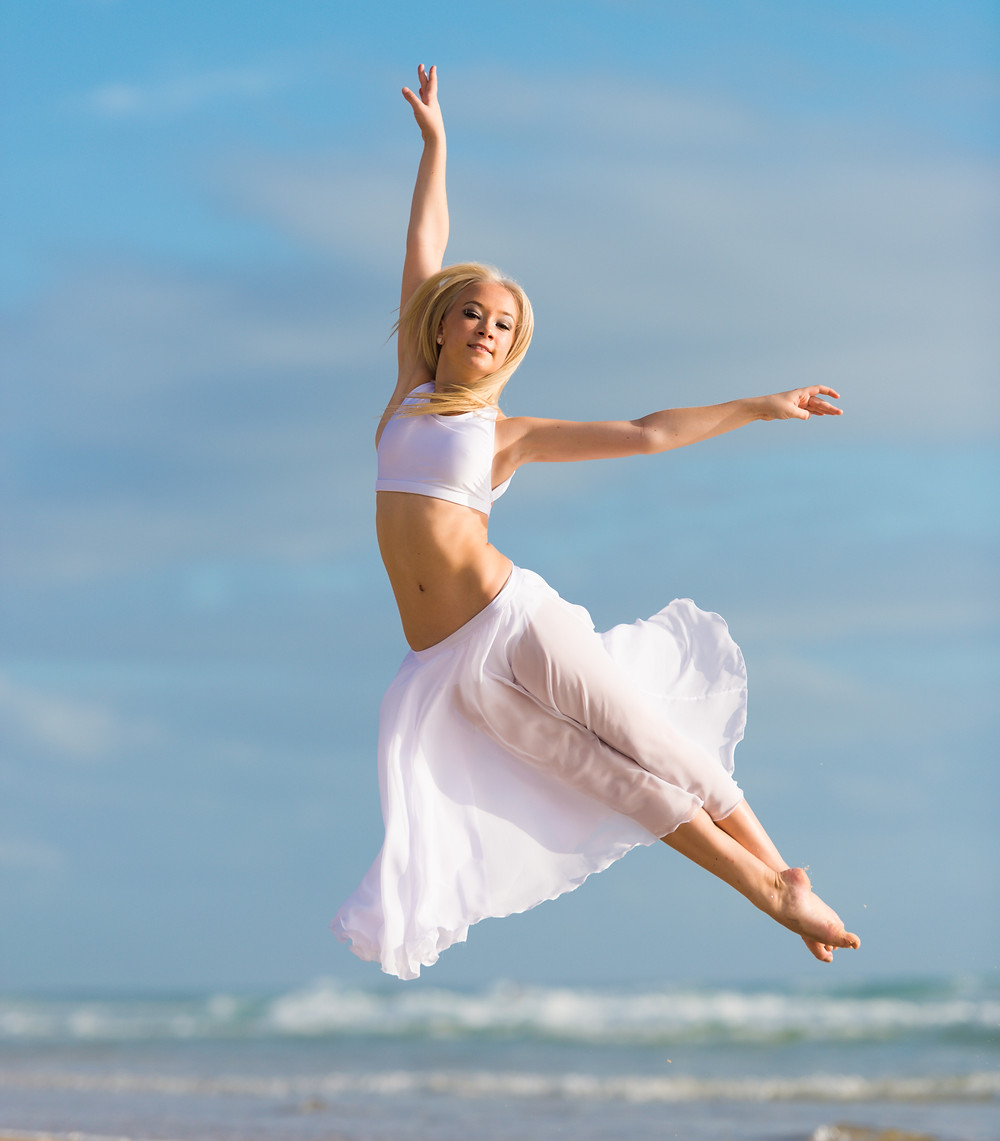 Dancer in white leaping with arms outstretched with sky and ocean background.