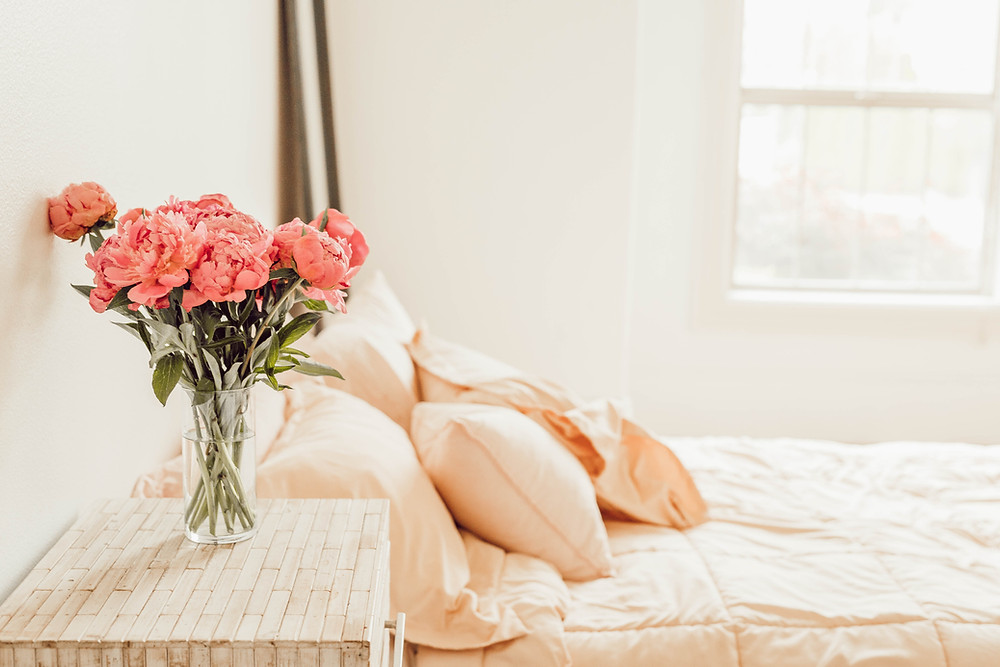 pink flowers- flowers in a vase-bed-pillow-peach colour-bedroom-relaxing bedroom-