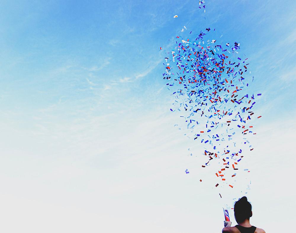 Confetti exploding across a blue sky