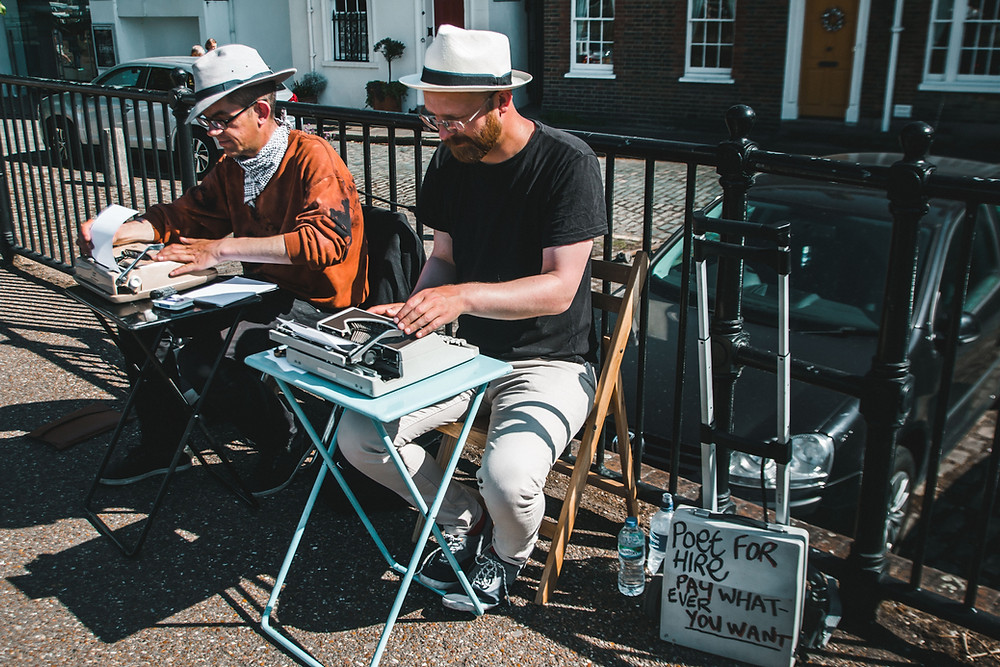 two men in hats typing on typewriters outside