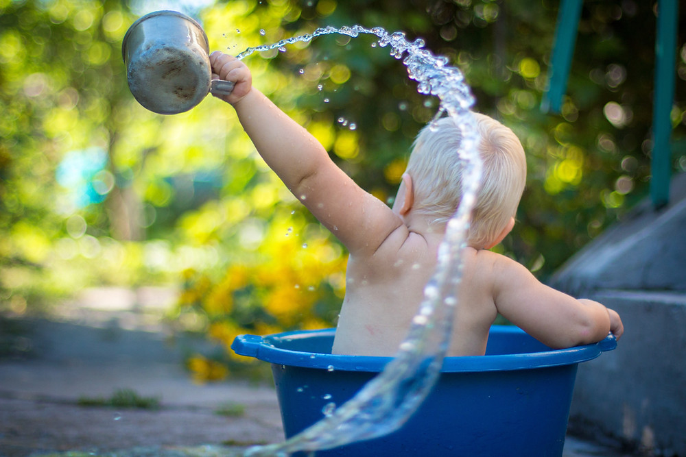 Infant playing with water in plastic tub