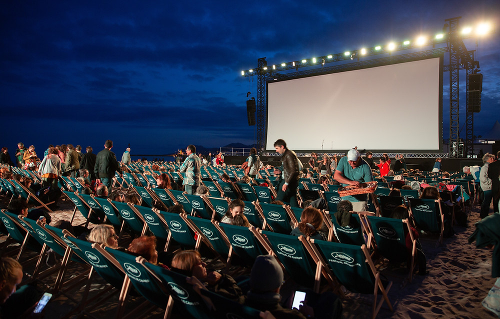 image shows deck chairs in front of a big screen. The deck chairs have the Cannes film festival logo on.