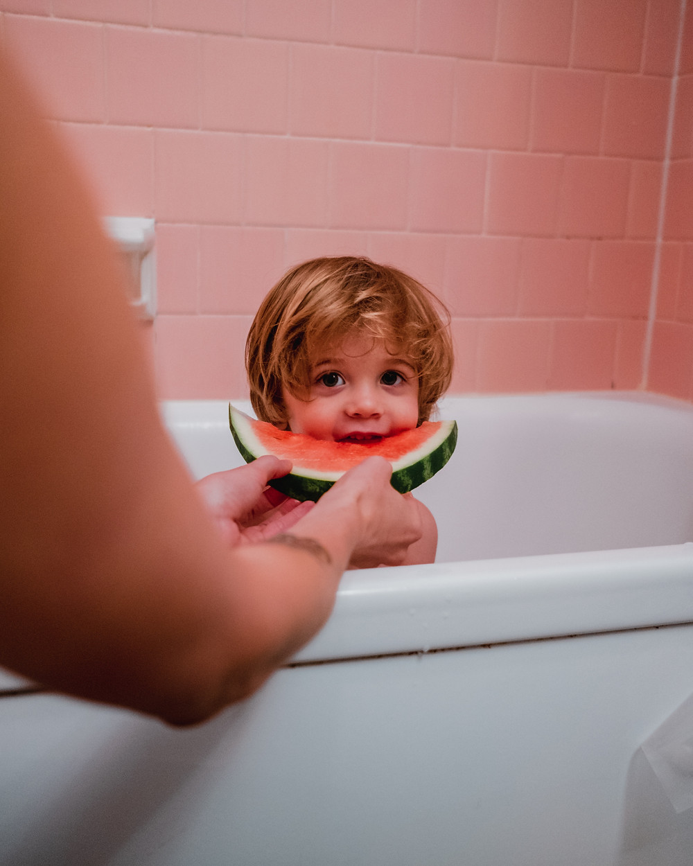 A child eating watermelon in the bath.