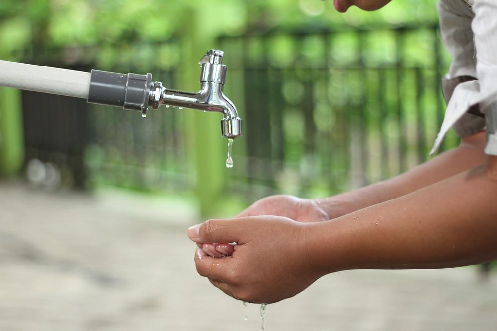 child hands under water