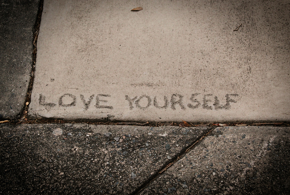 a piece of sidewalk with the words love yourself carved into it