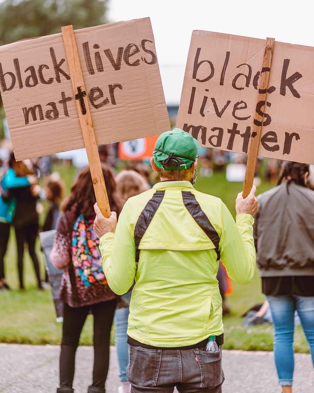 Image of a white person wearing waterproof jacket and hat facing away from the camera holding up two signs that say black lives matter.