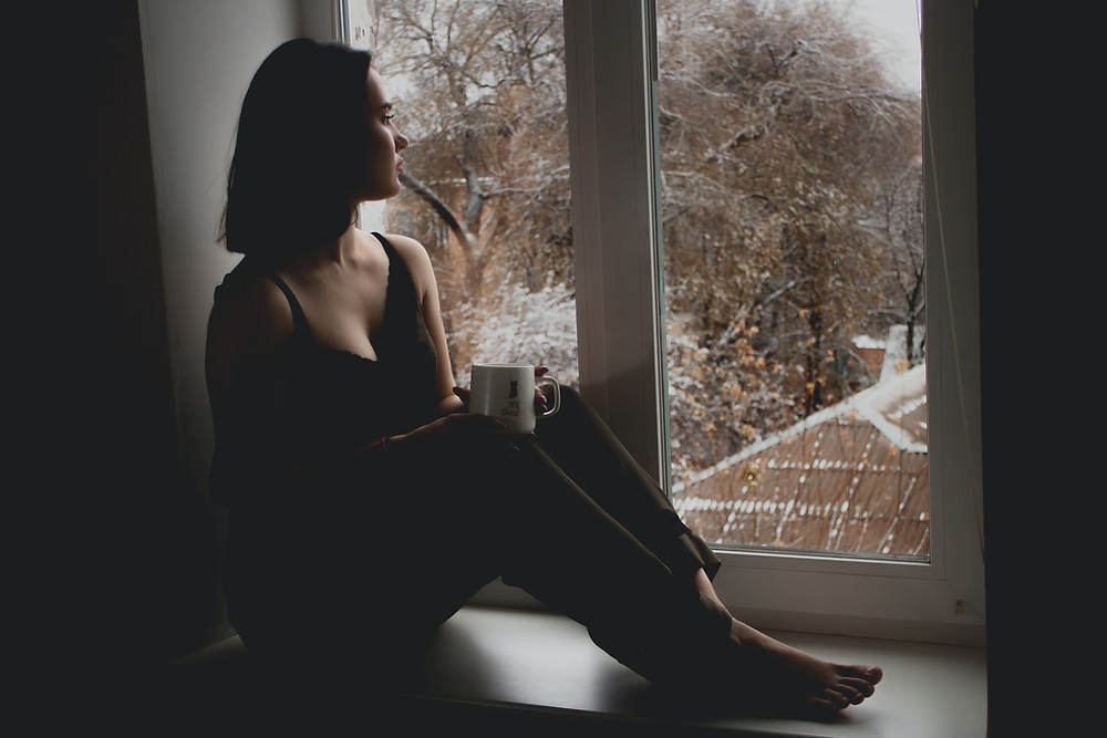tired woman looking out window